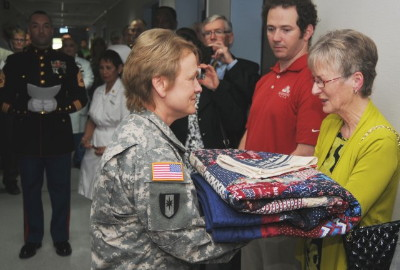 Maria Fox-Meehan receives a handmade quilt of valor during the dedication ceremony of The Thomas Meehan Suite